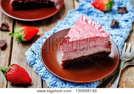 Strawberry mousse brownie cake on dark wood background.