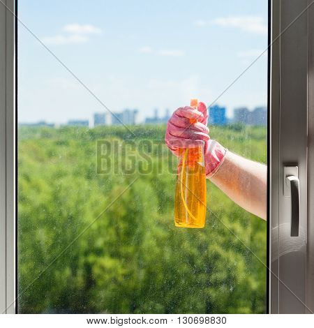 Hand Sprays Liquid From Spray Bottle To Window