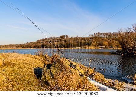 Fishing spinning on the background gorgeous landscape on the river