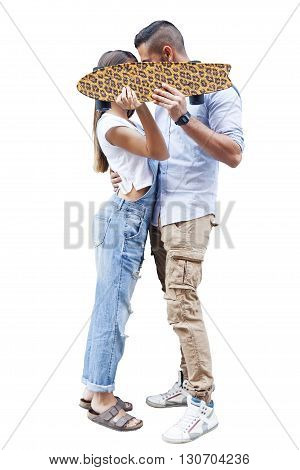 Young Couple Kissing Hiding Behind Skateboard Isolated On White Background
