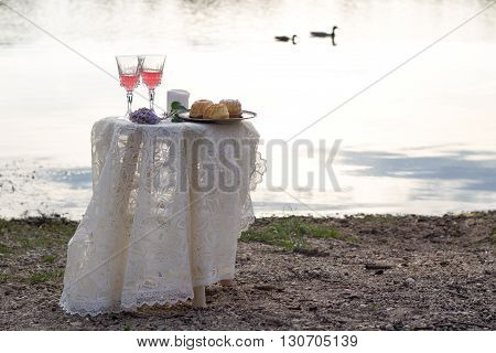 romantic table with pink wine and food outdoors