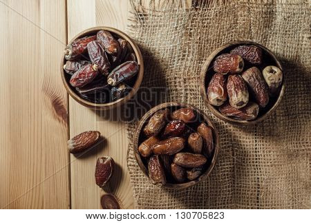 Different variety of ripened Saudi dates in various earthen bowls. View from above on grunge background.