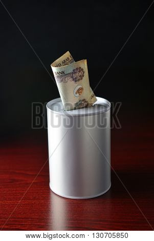 One thousand dirham note inserted in the saving can. Saving tin and UAE Dirham note. Stock photo.