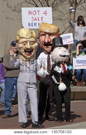 Asheville, North Carolina, USA - February 28, 2016: Parody of Donald Trump Hillary Clinton and Mr. Monopoly standing close together holding bags of money in front of Bernie Sanders campaign supporters holding signs saying that Bernie is not for sale