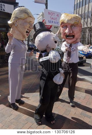 Asheville, North Carolina, USA - February 28, 2016: Parody of Donald Trump entreating Mr. Monopoly for his money as Hillary laughs in front of a Bernie Sanders campaign sign saying Bernie is not for sale on February 28, 2016 in downtown Asheville, NC