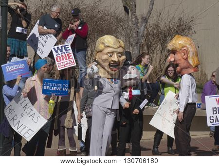 Asheville, North Carolina, USA - February 28, 2016: Effigies of Hillary Clinton and Mr. Monopoly hold bags of money and cozy up togeher as Donald Trump watches with a crowd of Bernie Sanders supporters with signs behind them