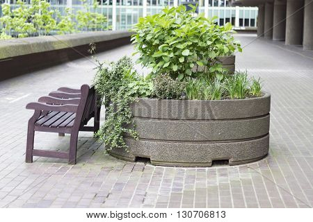 London England - May 19 2016: A bench and a plant granit pot in Barbican centre in London England.
