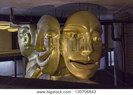 London England - May 19 2016: The Barbican Muse is a sculpture by Matthew Spender and represents a woman holding tragedy and comedy masks in London England.