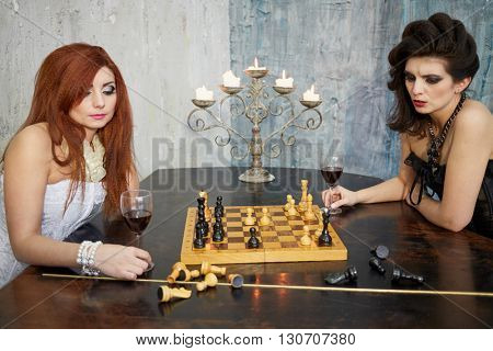 Red-haired woman in white dress and dark-haired woman in black dress play chess on the old grand piano lid in room with ragged walls.