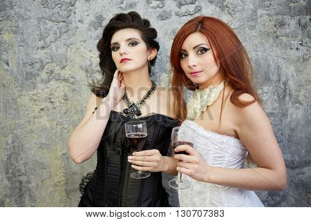 Red-haired woman in white dress and dark-haired woman in black dress stand with glasses of wine in room with ragged walls.