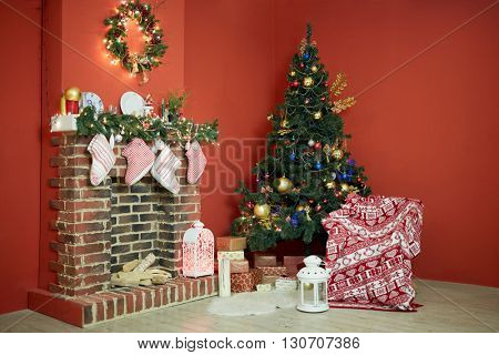 Interior of room with firtree decorated to christmas holidays, fireplace, red walls.