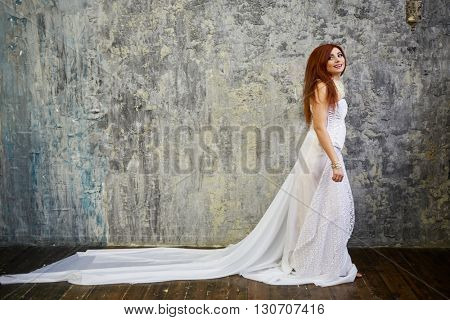 Red-haired woman in white dress with long skirt walks along wall in the ragged room.