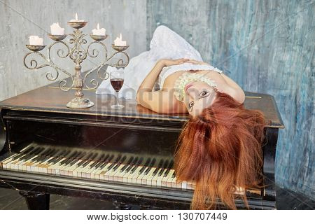 Red-haired woman in white dress lies with her eyes open on old black grand piano lid with candles and glass of red wine.