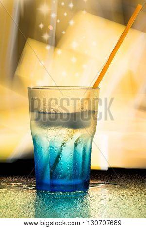 a blue wet glass with orange straw