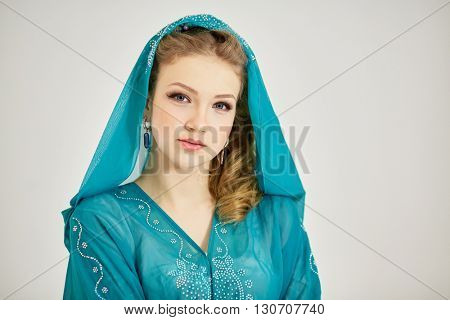Portrait of young woman in dress with hood on head.