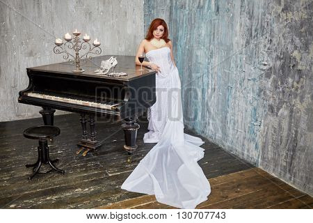 Red-haired woman in white dress stands leaning her elbow on grand piano lid with glass of red wine, burning candles, shoes and necklace in room with ragged walls.