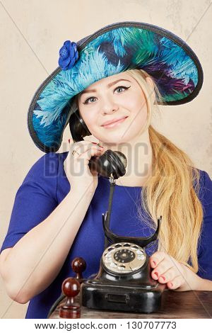Blonde in wide-brimmed blue ladies hat talks by retro phone at studio.