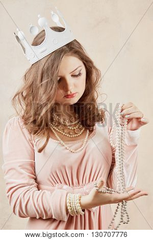 Young woman in pink dress with pearl necklace, beads and crown on head.