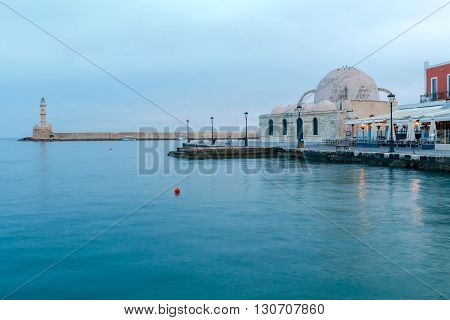 Scenic view of Venetian promenade with a lighthouse and the mosque Kucuk Hasan Pasha in the early morning, Crete, Greece.