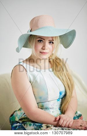 Portrait of young blond woman in wide-brimmed hat on couch in studio.
