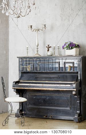 Old piano with candlesticks and wicker basket full of flowers on the upper lid in room.