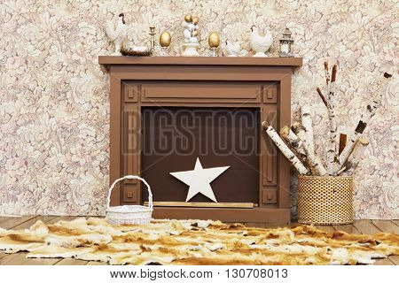 Decorative wooden mantlepiece with star, hen, rooster, eggs, basket with firewood, foxcases on the floor.