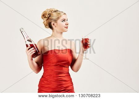 Young woman in red dress with bottle of wine in one hand and wineglass in another.