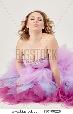 Portrait of woman in a fluffy purple dress giving an air kiss.