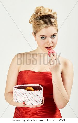 Woman in red dress holds open box in shape of heart and going to bite off cookie.