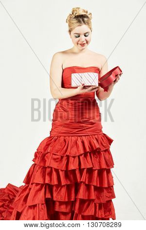 Smiling woman in red dress looks into open box in shape of heart.
