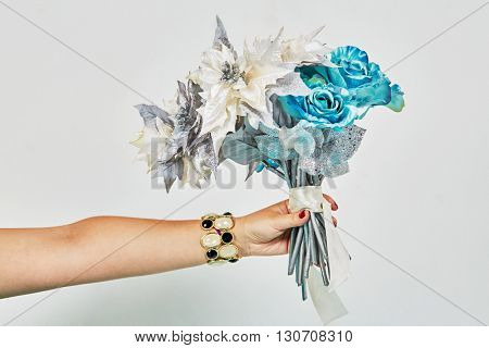 Outstretched female hand with bracelet holds bunch of artificial flowers.