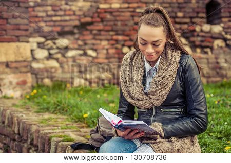 Beautiful young woman reading book on the wall of fortress