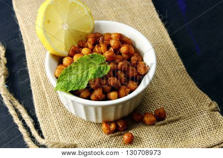 Roasted Chickpeas with cumin salt red chilli powder and lemon in a bowl on a wooden background with copy space