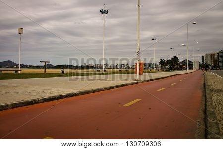 Red road with beach on background and light poles
