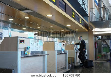 VALENCIA, SPAIN - MAY 21, 2016: An airline passenger checking in at an airline counter in the Valencia Airport. About 4.98 million passengers passed through the airport in 2015.