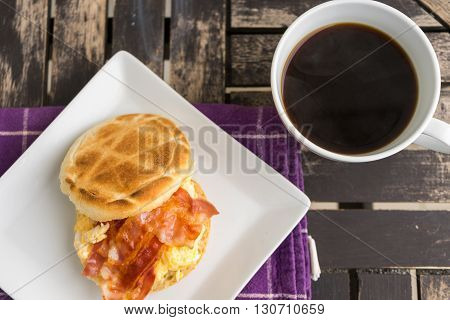 Salt muffin with scrambled eggs bacon and cheese on white plate with dark coffee in white mug lying on wooden background. Unhealthy breakfast with bacon eggs pastry and coffee on purple dishtowel. Flat view.