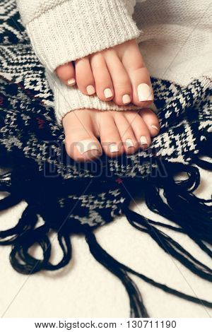 Beautiful beige pedicure. Feet in soft knitted socks black plaid with ornament