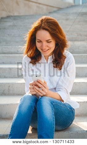 Girl with a phone in her hands, sitting on the steps, writes sms. Online shopping concept