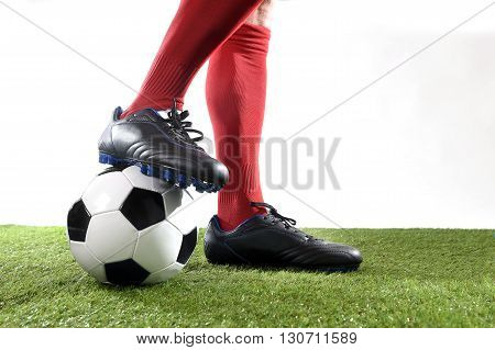 close up legs and feet of football player in red socks and black shoes playing with the ball on green grass pitch isolated on white background