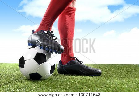 close up legs and feet of football player in red socks and black shoes playing with typical ball standing on green grass pitch outdoors isolated on blue sky background