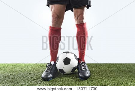 close up legs and feet of football player in red socks and black shoes posing with the ball playing on green grass pitch isolated on white background