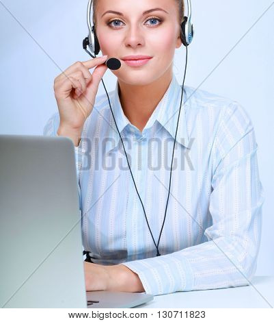 Portrait of beautiful businesswoman working at her desk with headset and laptop.