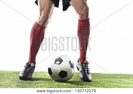 close up legs and feet of football player in red socks and black shoes running and dribbling with the ball playing on green grass pitch isolated on white background