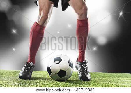 close up legs and feet of football player in red socks and black shoes running and dribbling with the ball playing on stadium pitch with background flashes and light flares