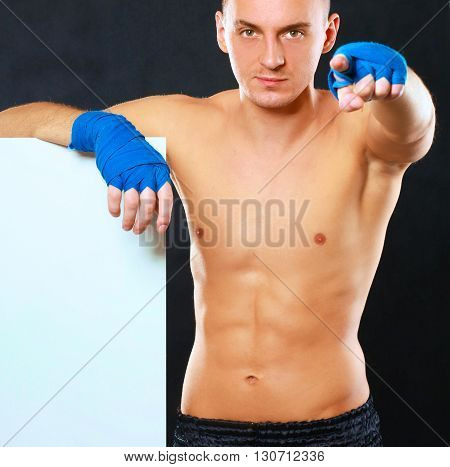 Young handsome boxer man standing near board and pointing at you, isolated on black background.