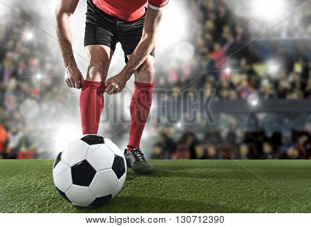 close up legs of football player with ball wearing black shoes adjusting his red sock standing on stadium pitch with background flashes and light flares