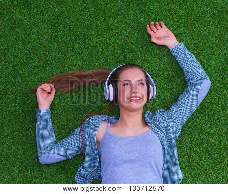 Relaxed woman listening to the music with headphones lying on the grass .