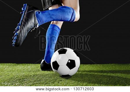 close up legs and feet of football player in action wearing blue socks and black shoes running and dribbling with the ball playing on green grass pitch isolated on black background