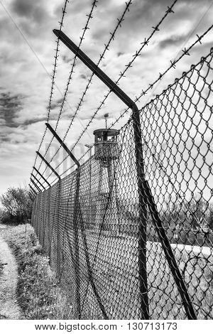Abandoned watchtower isolated by a net topped with barbed wire.