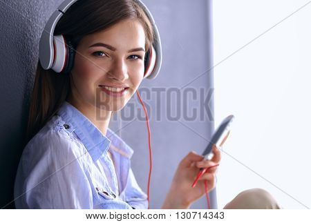 Smiling girl with headphones sitting on the floor near wall.